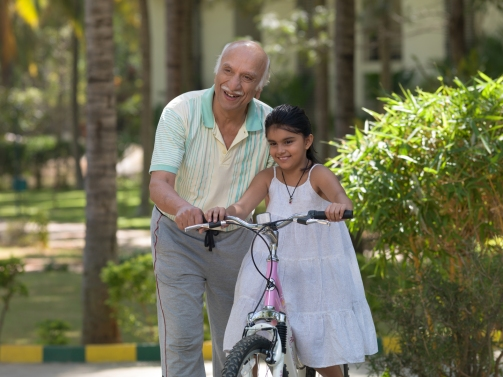Grandfather Teaching Daughter How To Cycle